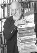 black and white photograph of James Loewen holding a stack of books he has authored