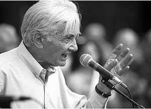 a black and white photograph of Howard Zinn addressing the crowd